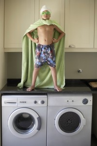 boy standing on high efficiency washers